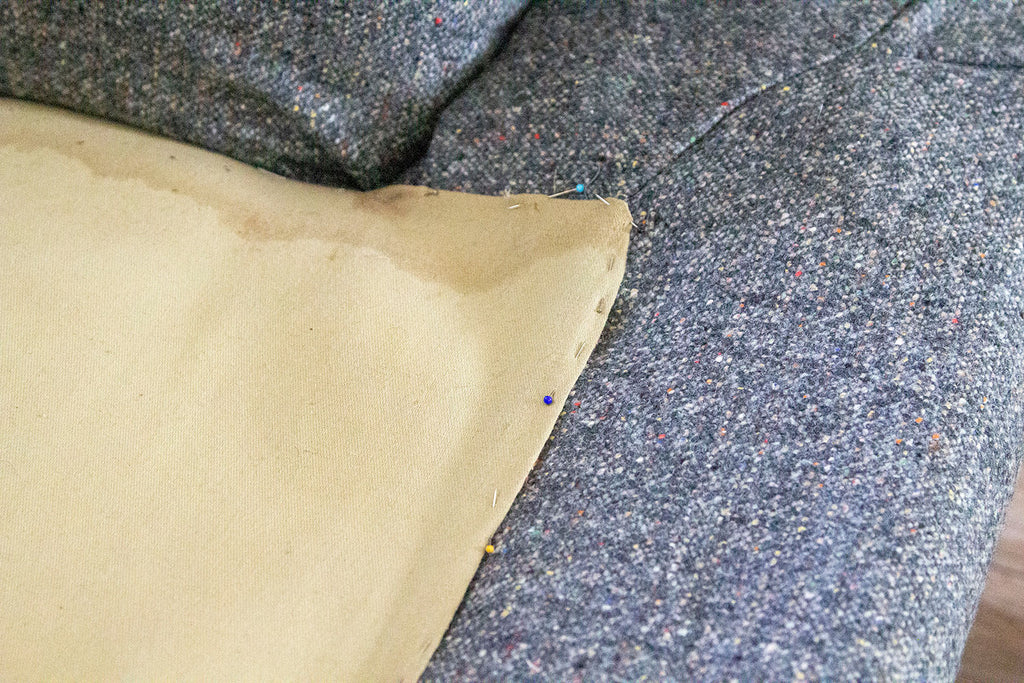 A close up of the lower couch's taupe fabric pinned to the new grey fabric prior to being hand sewn shut
