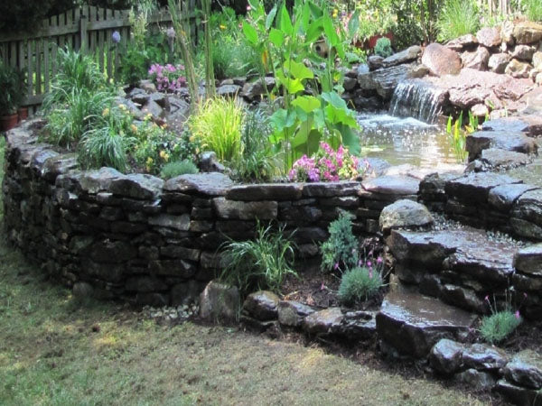 A pond built on top of a flat rock stacked retaining wall with a soft waterfall feature to the side.