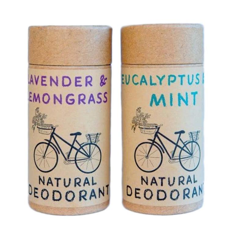 """Two cardboard cylinders that say """"Natural deodorant"""" across the bottom with images of bikes just above them. The one on the left reads """" Lavender and Lemongrass"""" in purple above the bike and the one on the right reads """" Eucalyptus Mint"""" in blue above its bike"""