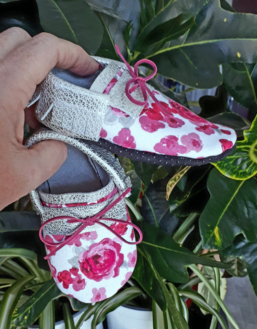Silver leather moccs with short fringe and pink floral toe toppers.