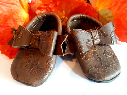 Floral embossed brown leather moccs with short fringe and bows