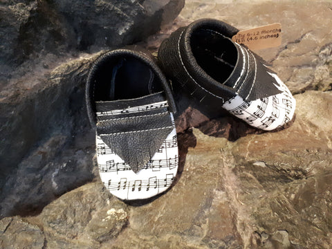 Black or grey leather moccs with short fringe and music toe toppers.