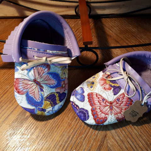 Lavender leather moccs with short fringe and butterfly print toe toppers.