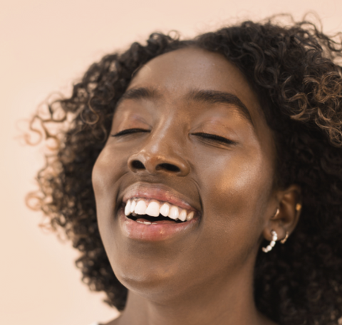 black woman smiling, wearing hyper clear face serum