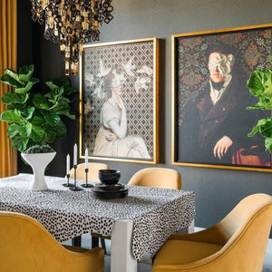 See No Evil by Jackie Von Tobel is a print of a gentleman whose vision is obscured by an artfully tied bow made of satin, in a modern dining room setting hanging.