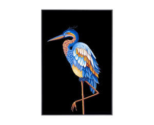 Heron II is a print by Jackie Von Tobel with a prowling bird on a black background in bright blue, yellow, and pale orange hues, the piece of wall art framed in black.