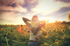young woman walking in a field of sunflowers