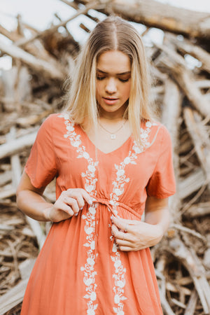The Walsh Embroidered Maxi Dress in Rust, lifestyle shoot; closer up shot front view