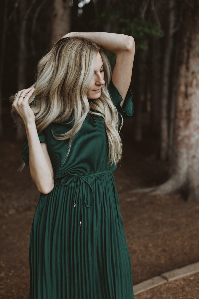 Piper & Scoot: The Versus Pleated Midi Dress in Emerald, lifestyle shoot; front view