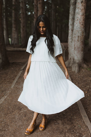 Piper & Scoot: The Hepburn Bib Dress in Ivory, lifestyle shoot; front view