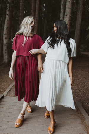 Piper & Scoot: The Hepburn Bib Dress in Ivory, lifestyle shoot; front view with friend