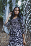The Mena Dot Patterned Smocked Dress in Black, lifestyle shoot; front view