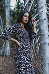 The Mena Dot Patterned Smocked Dress in Black, lifestyle shoot; side view