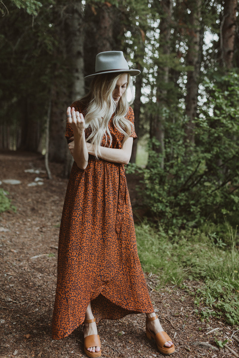 The Elise Patterned Wrap Dress in Rust, lifestyle shoot; front view