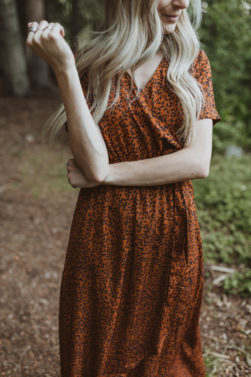 The Elise Patterned Wrap Dress in Rust, lifestyle shoot; closer up front view