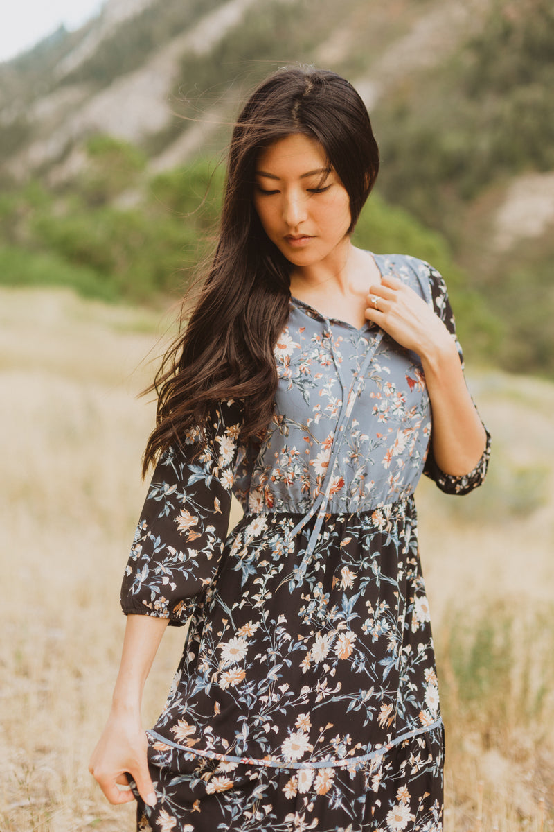 The Haskell Floral Contrast Maxi Dress in Black, lifestyle shoot; closer up front view