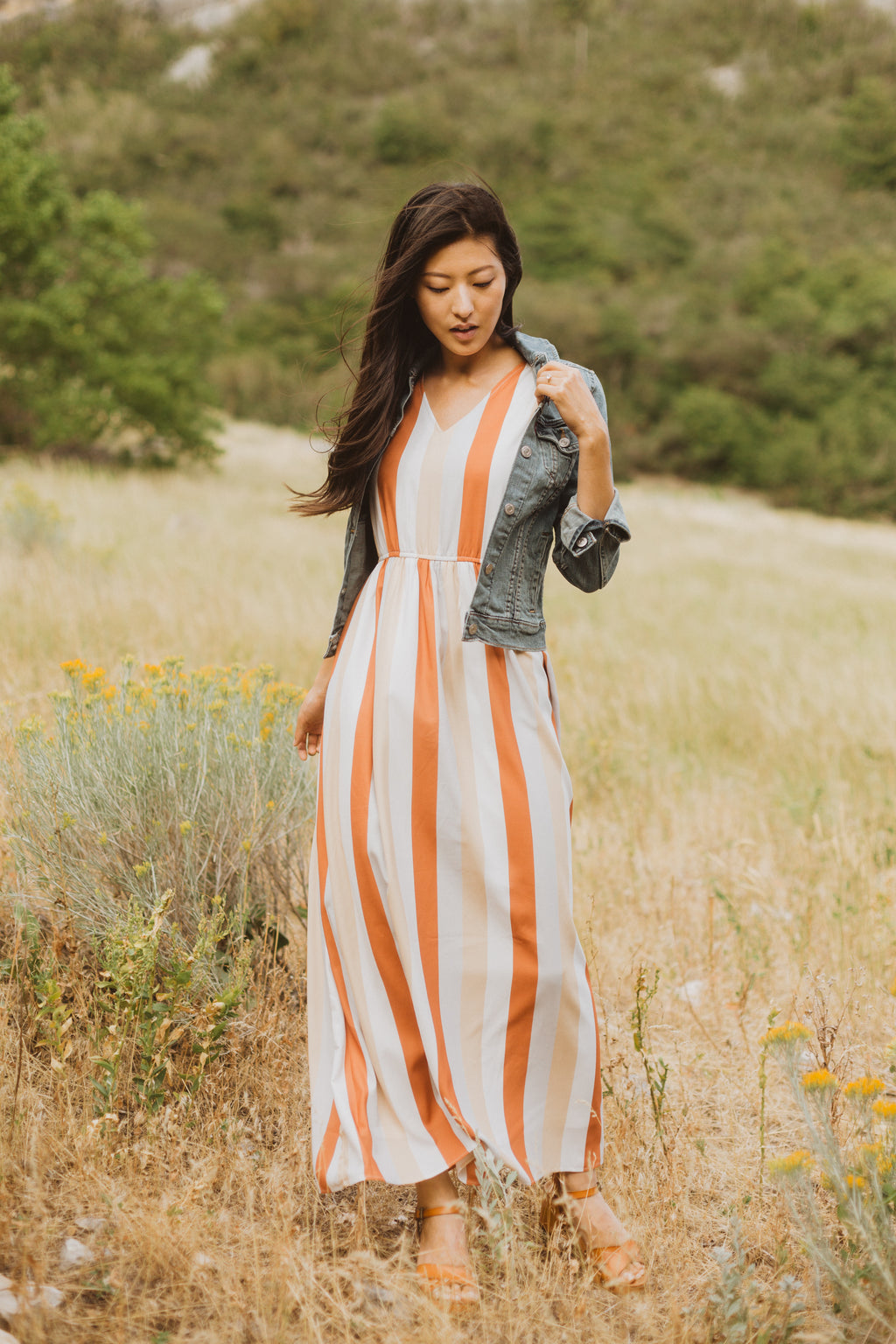 The Butler Striped Maxi Dress in Multi, lifestyle shoot; front view paired with denim jacket