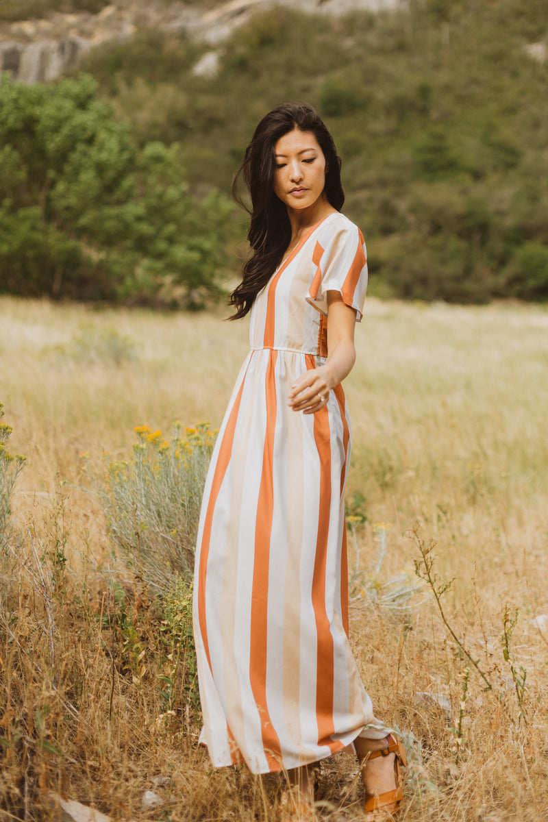 The Butler Striped Maxi Dress in Multi, lifestyle shoot; side view