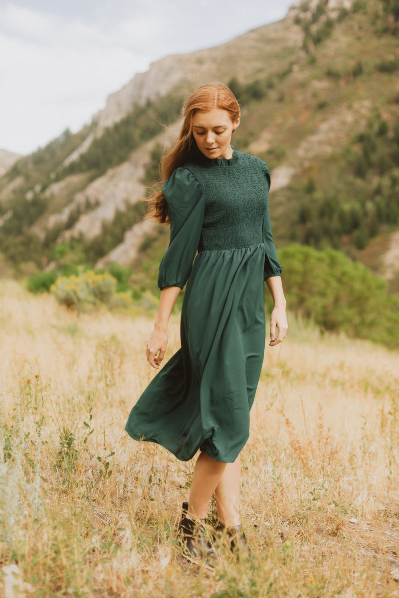 The Ezra Smocked Midi Dress in Hunter Green, lifestyle shoot; front view