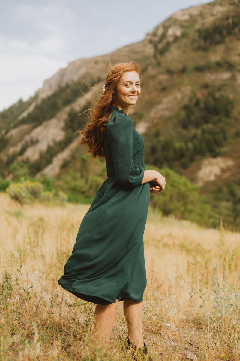 The Ezra Smocked Midi Dress in Hunter Green, lifestyle shoot; side view