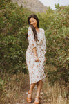 The Watts Floral Pleated Wrap Dress in Ivory, lifestyle shoot; front view