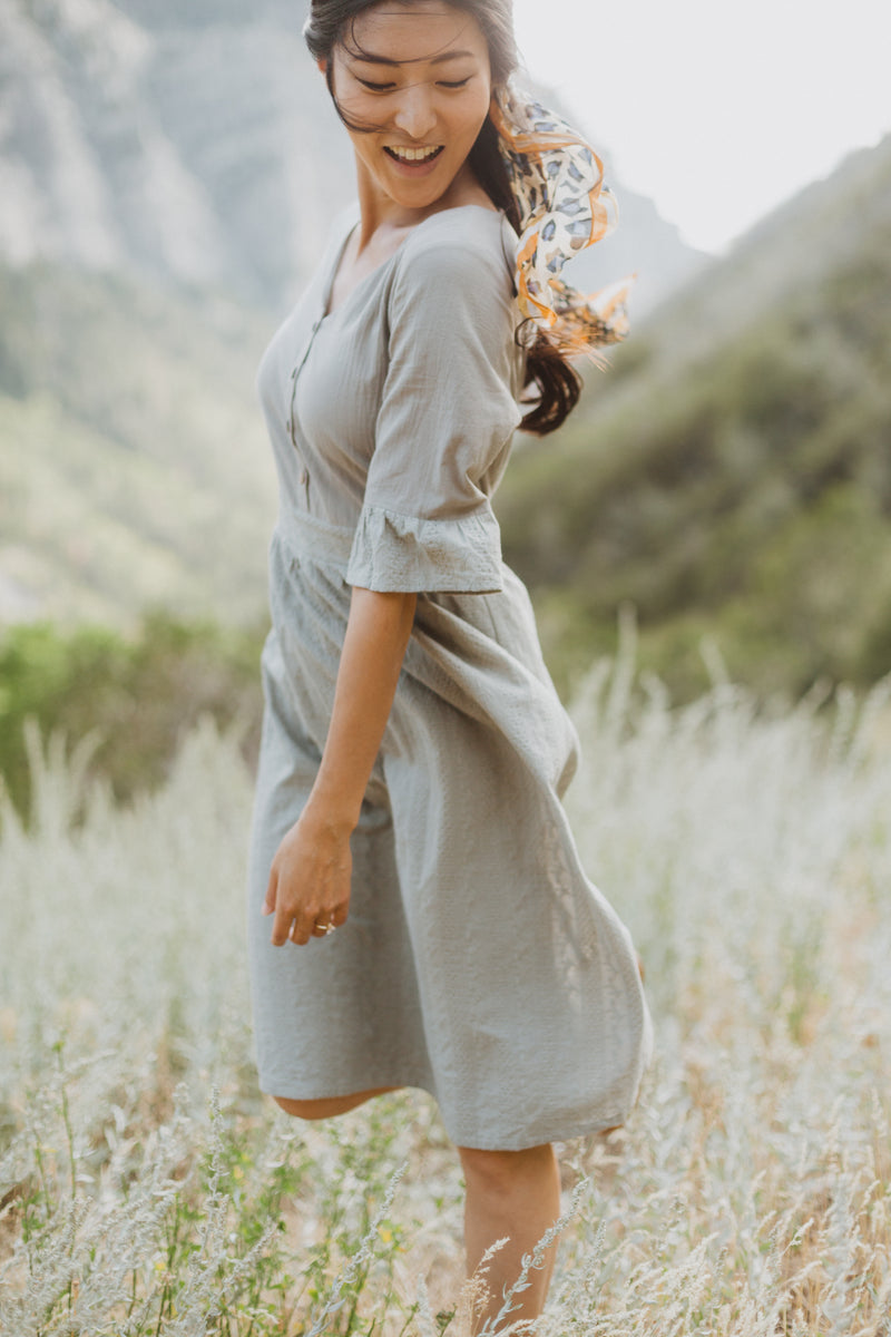 The Colby Ruffle Detail Dress in Sage, lifestyle shoot; side view