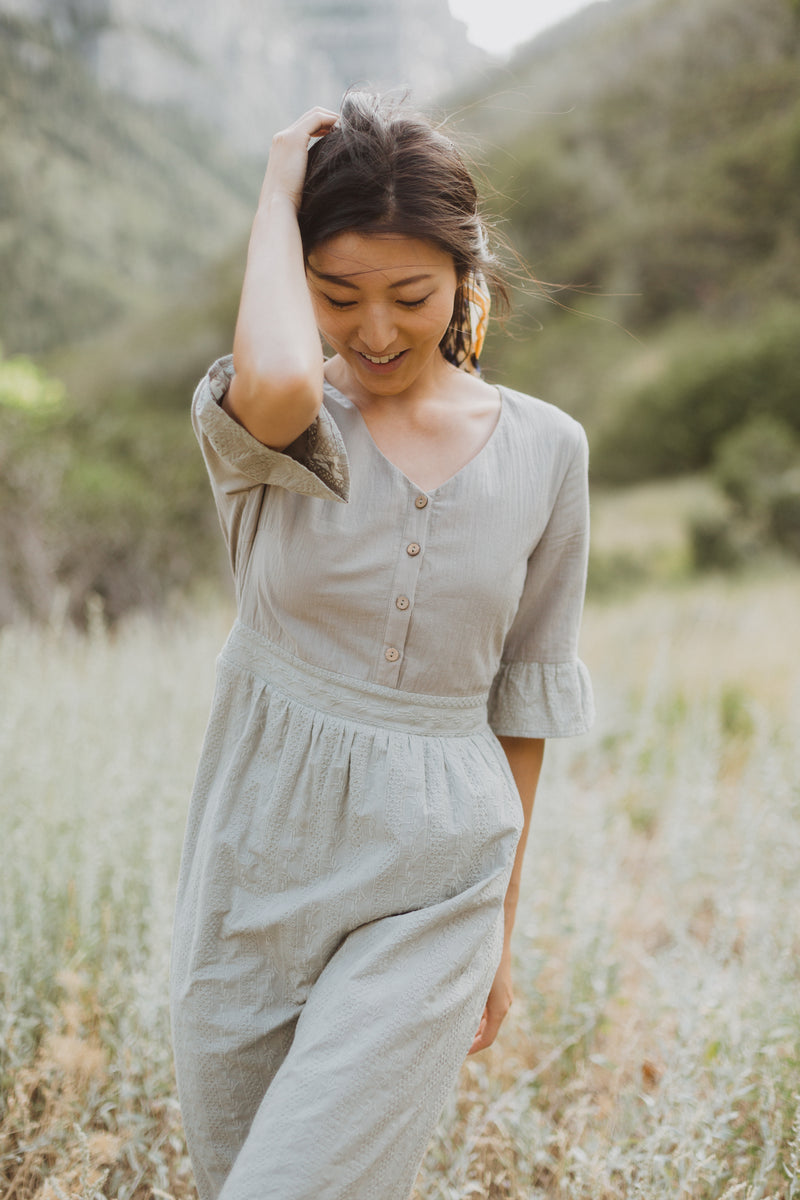 The Colby Ruffle Detail Dress in Sage, lifestyle shoot; front view