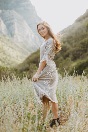 The Imagine Lace Dress in Grey, lifestyle shoot; side view