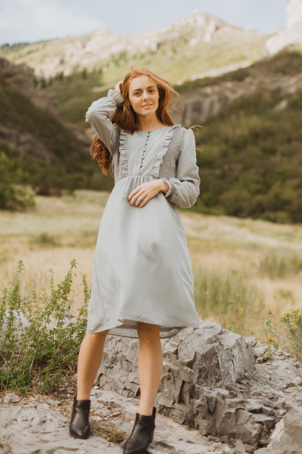 The Branly Ruffle Bib Dress in Sage, lifestyle shoot; front view