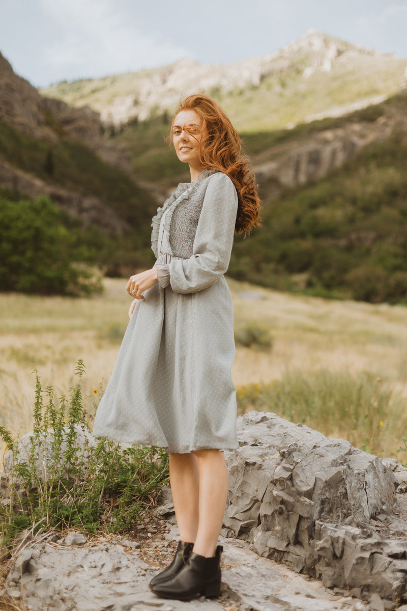 The Branly Ruffle Bib Dress in Sage, lifestyle shoot; side view