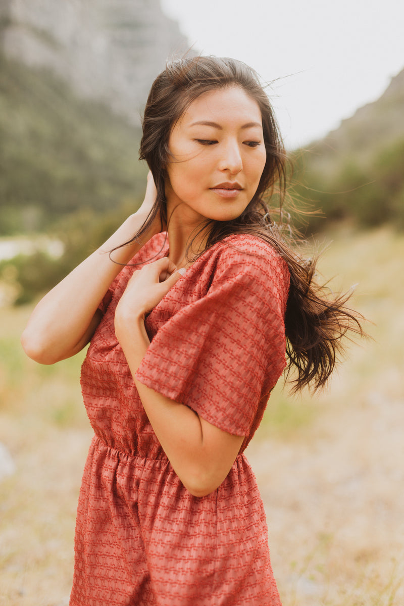 The Romy Patterned Ruffle Dress in Burgundy, lifestyle shoot; side view