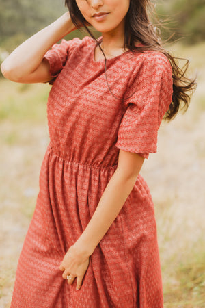 The Romy Patterned Ruffle Dress in Burgundy, lifestyle shoot; front view