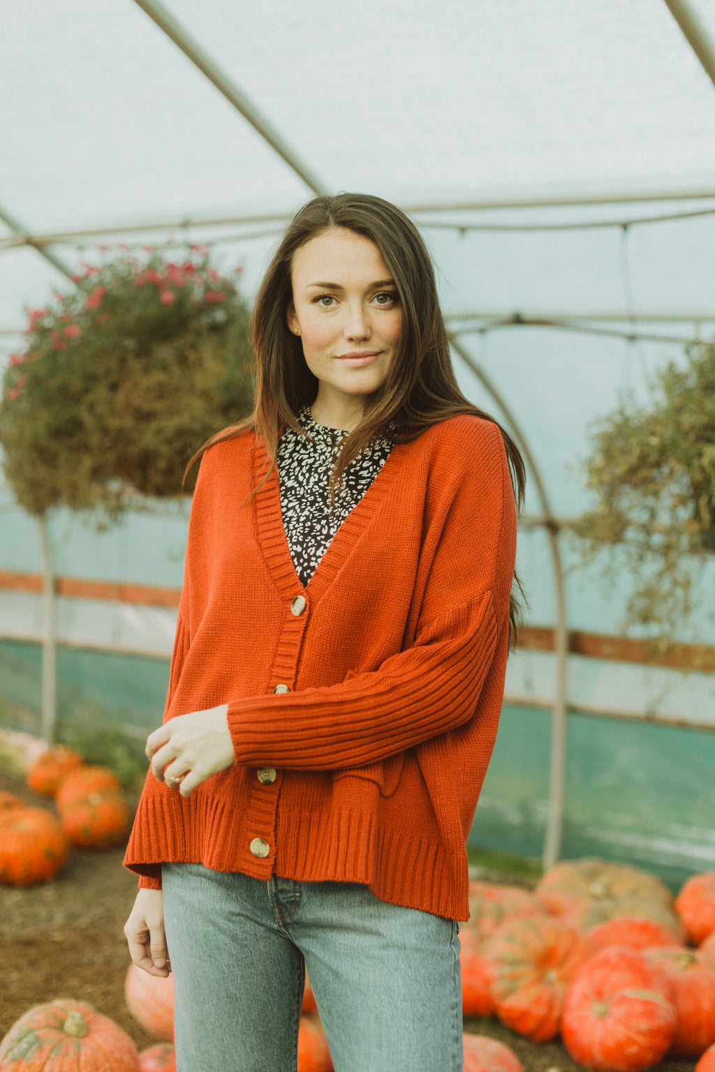 The Saylor Ribbed Button Sweater in Brick, lifestyle shoot; front view