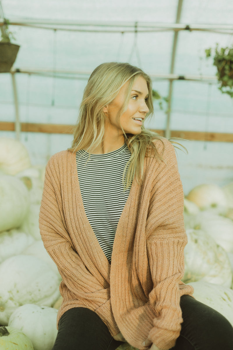 The Ames Ribbed Cardigan in Rose, lifestyle shoot; front view