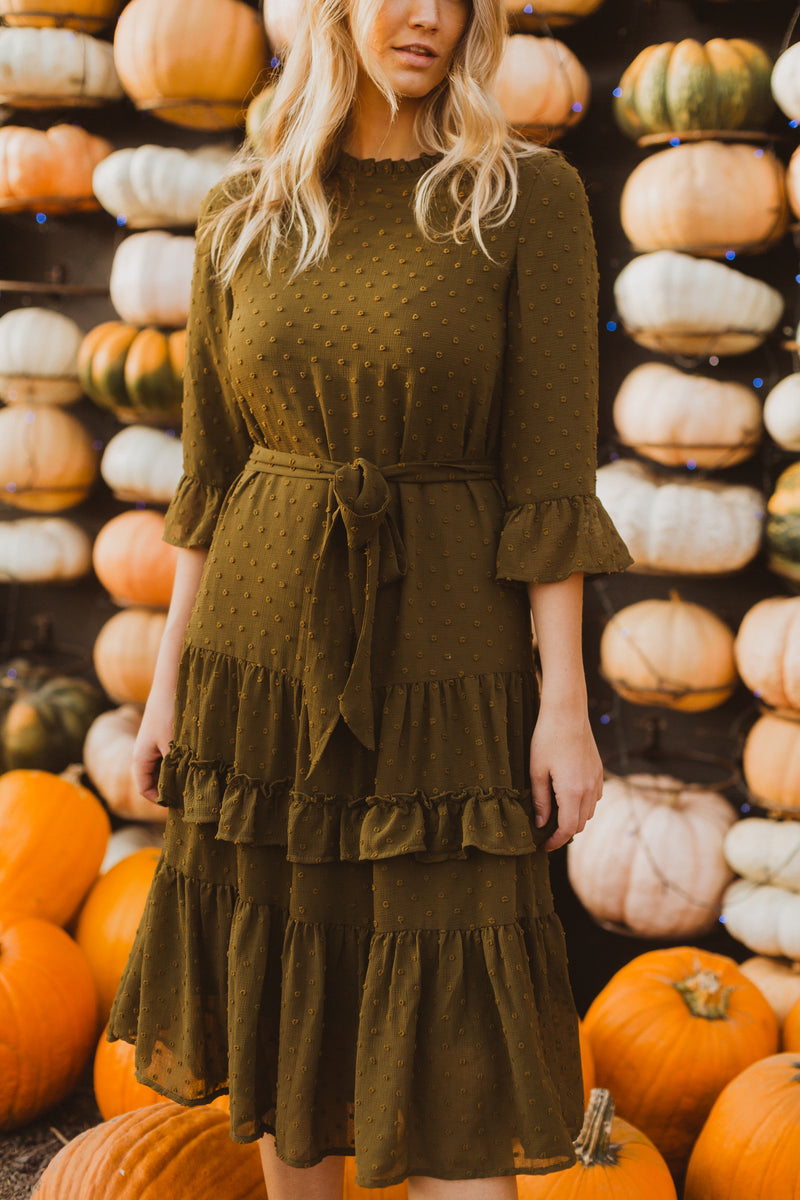 The Hallie Swiss Dot Ruffle Dress in Moss, lifestyle shoot; closer up front view