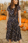 The Percey Floral Pleated Dress in Navy, lifestyle shoot; front view