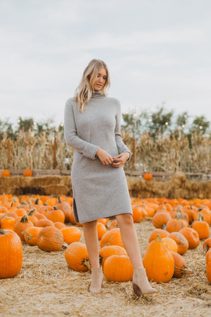 The Revive Ribbed Turtleneck Sweater Dress in Heather Grey, lifestyle shoot; front view