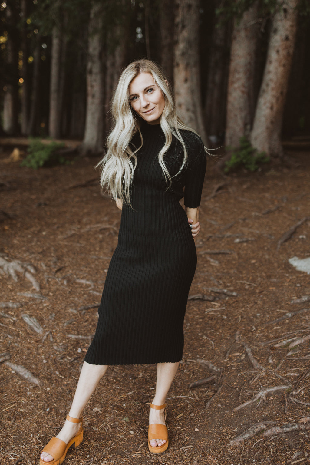 The Eugene Ribbed Sweater Dress in Black, lifestyle shoot; front view