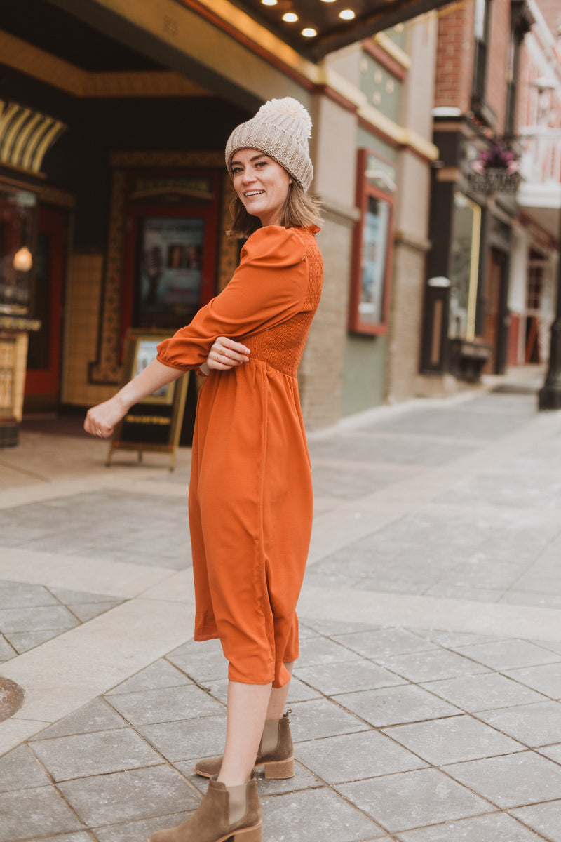 The Ezra Smocked Midi Dress in Rust, lifestyle shoot; side view
