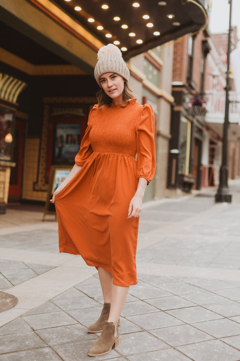 The Ezra Smocked Midi Dress in Rust, lifestyle shoot; front view
