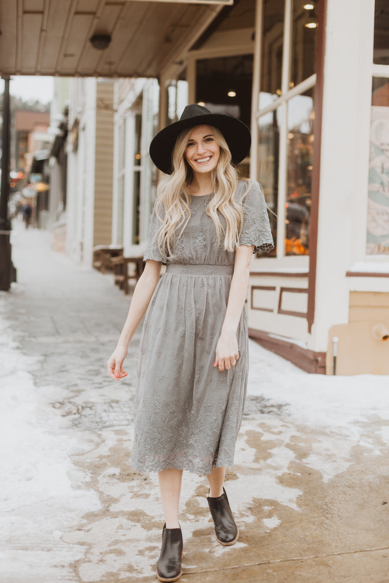 The Charming Lace Detail Dress in Grey, lifestyle shoot; front view paired with hat
