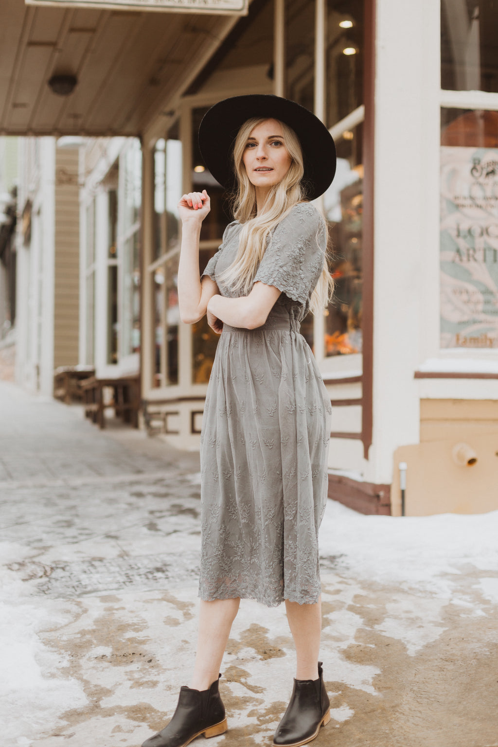 The Charming Lace Detail Dress in Grey, lifestyle shoot; side view paired with hat