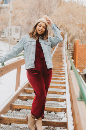 Piper & Scoot: The Bianca Cinch Velvet Jumpsuit in Burgundy, lifestyle shoot; front view paired with denim jacket