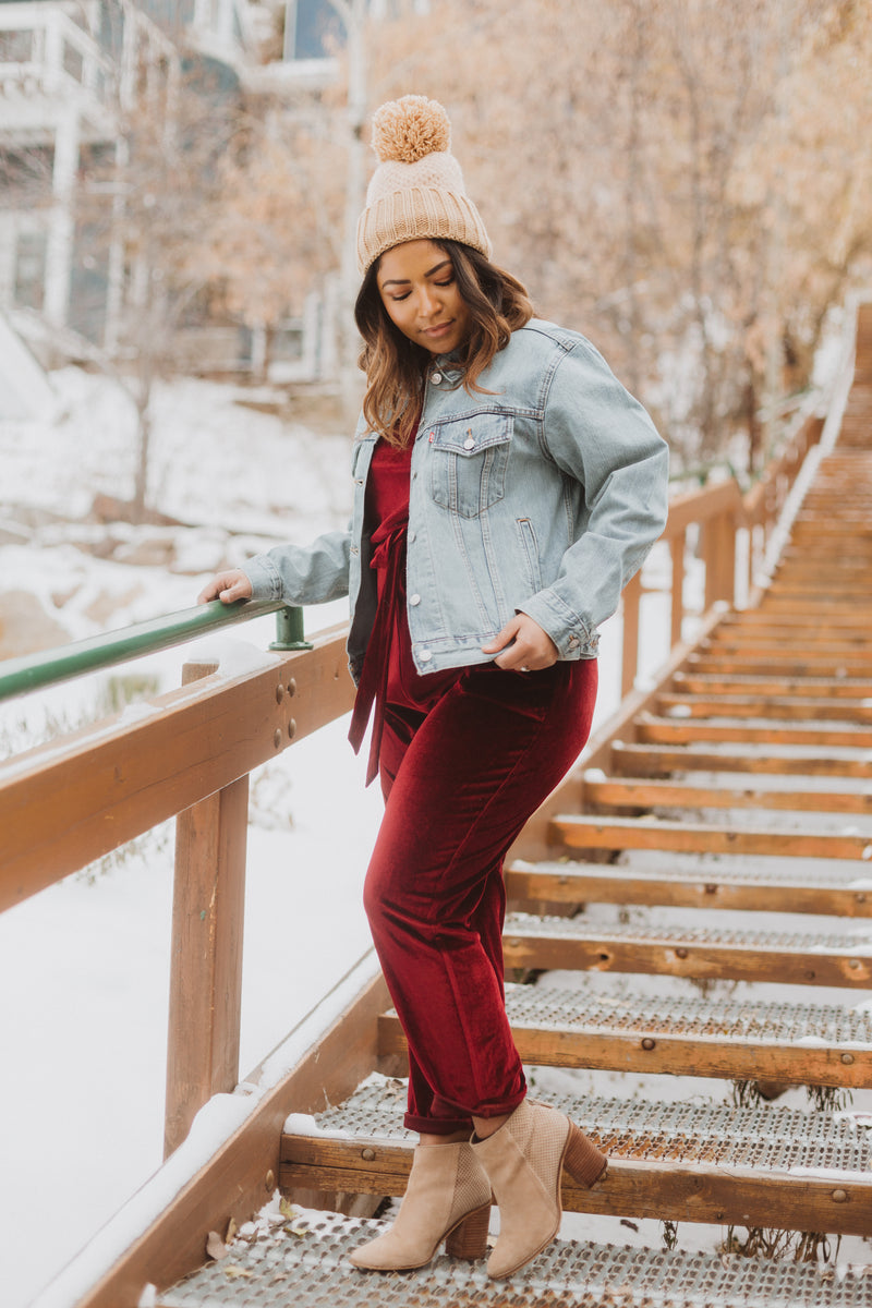 Piper & Scoot: The Bianca Cinch Velvet Jumpsuit in Burgundy, lifestyle shoot; side view paired with denim jacket