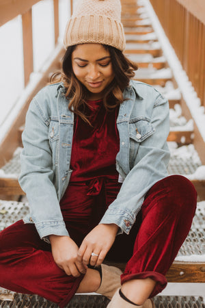 Piper & Scoot: The Bianca Cinch Velvet Jumpsuit in Burgundy, lifestyle shoot; sitting front view paired with denim jacket