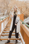 Piper & Scoot: The Bianca Cinch Velvet Jumpsuit in Black, lifestyle shoot; front view paired with cardigan