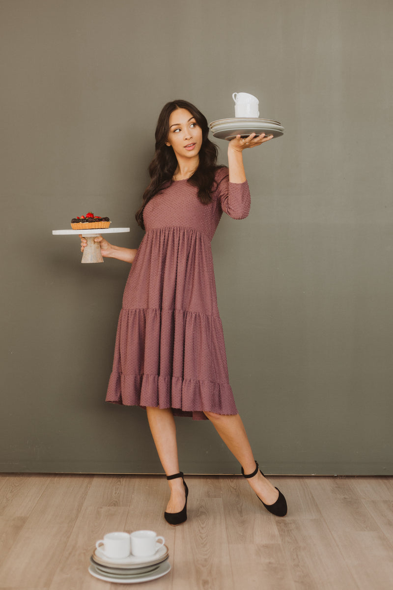 The Grantley Tiered Swiss Dot Dress in Plum, studio shoot; front view styled with cake stands
