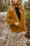 The Clarise Open Pocket Cardigan in Mustard, lifestyle shoot; front view