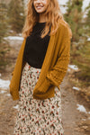 The Clarise Open Pocket Cardigan in Mustard, lifestyle shoot; side view
