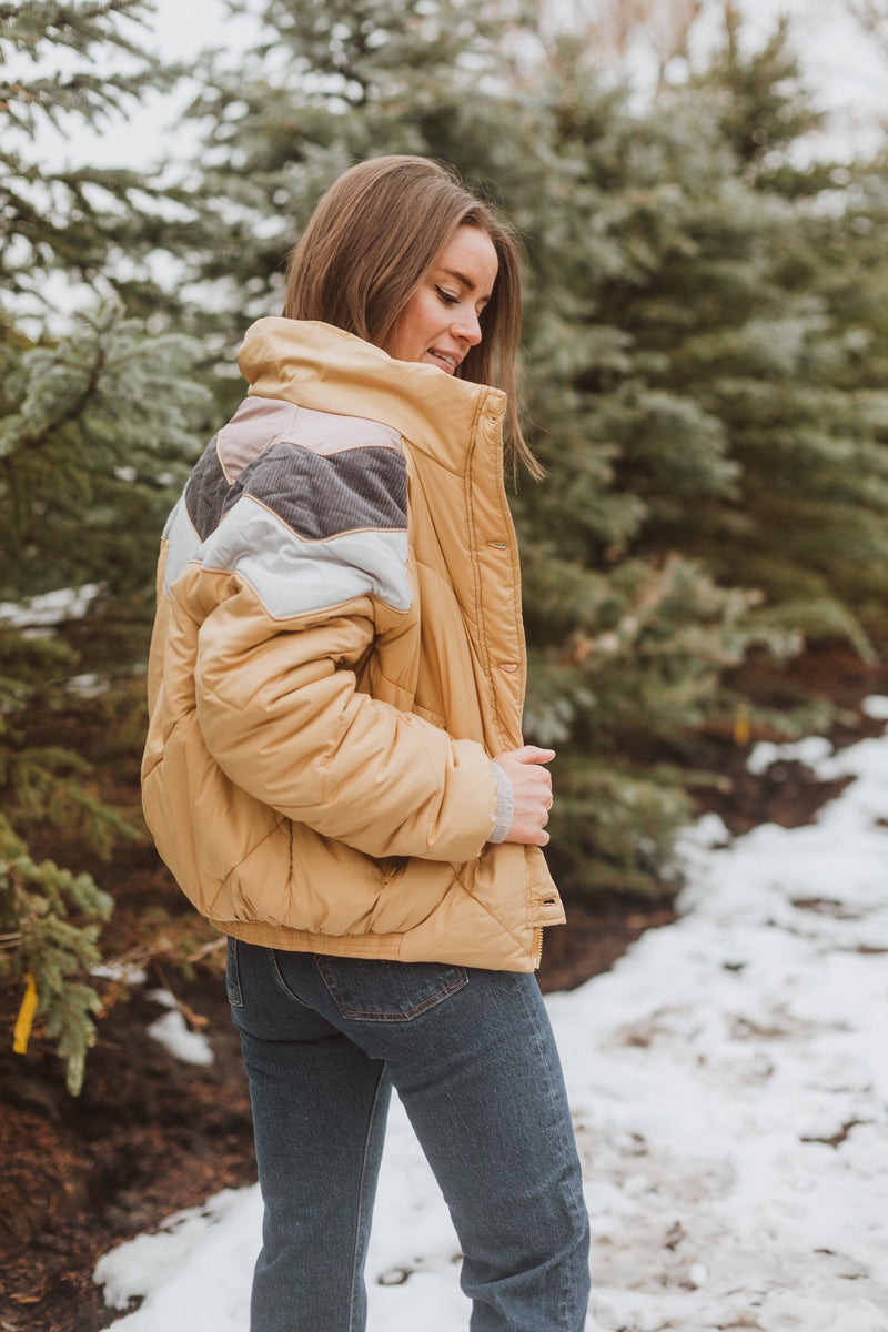The Babita Padded Bomber Jacket in Mustard, lifestyle shoot; side view